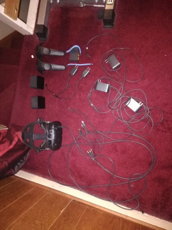 HTC VIVE HEADSET WITH AUDIO STRAP, WIRES, LINK BOX, CONTROLLERS AND SENSORS.