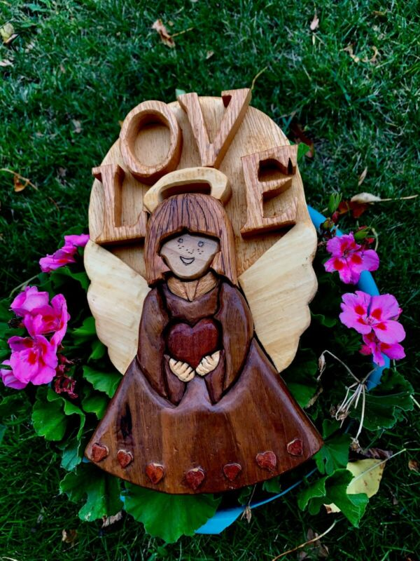 """wooden hand carved Angel embrace heart with the word"""" LOVE"""" on a wooden planle"""