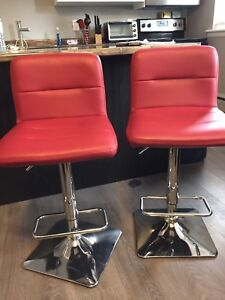 Two red leather bar stools