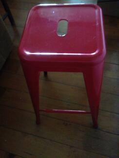 Two red metal bar stools