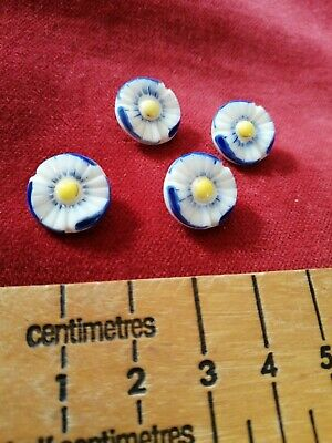 FOUR VINTAGE ANTIQUE white glass painted flowers detailed shanked small buttons.