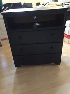 Commode noir avec roulettes pouvant servir de meuble de TV.