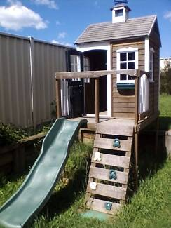 Wooden cubby house with slide
