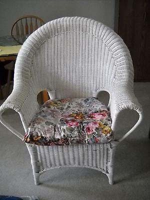 White wicker arm chair with Ralph Lauren cushion ()