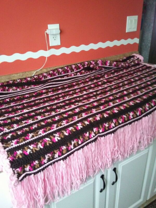 handmade crocheted afghan done in pink multi and brown