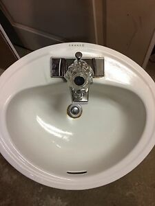 White enamel bathroom sink with single handle faucet
