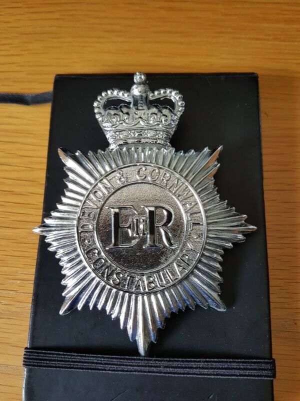 DEVON & CORNWALL POLICE DISCONTINUED HELMET BADGE WITH ITS REAR CENTRE FIXING.