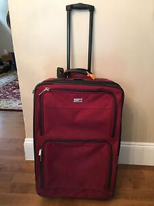 Red suitcase with wheels and handle