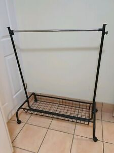 Black solid laundry trolley rack for hanging clothes.