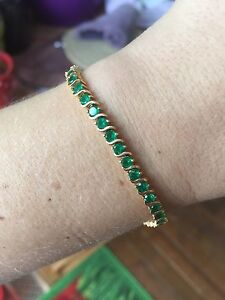 Ladies 18k gold and Emerald tennis bracelet