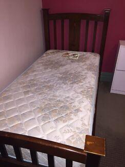 Dark wooden bed frame with mattress
