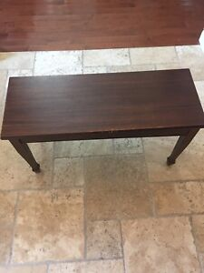 Wooden piano bench with assorted piano books