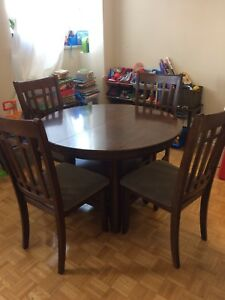 Round brown wooden table with six chairs dining room set