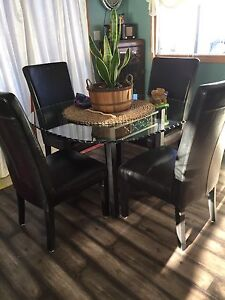 Round glass table with four black leather chairs