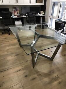 Modern glass table with stainless steel base. Custom made