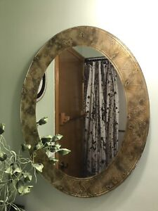 Two gold oval mirrors