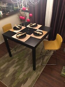 I am selling high dining table with 2 yellow chairs. $300