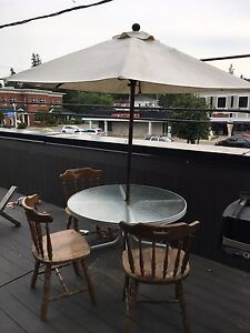 Glass patio table / Umbrella and 3 wooden chairs