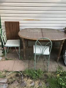 Old used dining table with two old used chairs.