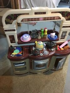 Toy kitchen with pans, pots, kitchen dishes and toys included.