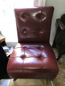 Two red faux leather chairs.