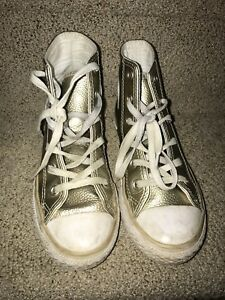 Gold and white converse shoes