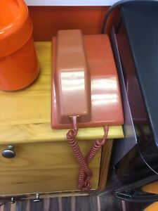Collection of orange rotary phones telephones