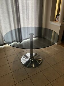 Glass dining table with chrome tulip base.