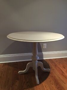 Round wood desk or accent table, painted light grey.