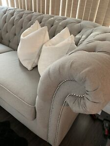 Tufted grey couch with studs.
