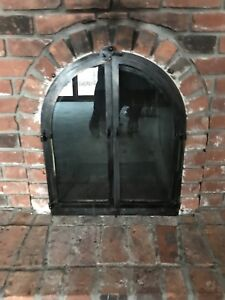 Arched wood fireplace door