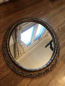 Oval shaped mirror with gold decorative trim