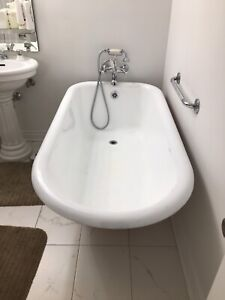 Antique cast iron clawfoot bathtub with faucet and curtain rod