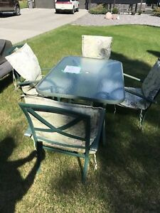 Glass patio table with 4 chairs and cushions.