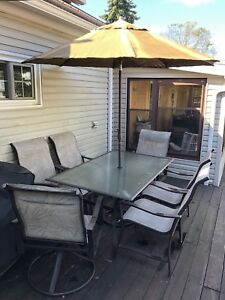 PATIO TABLE , 6 CHAIRS, 2 THAT SWIVEL & UMBRELLA