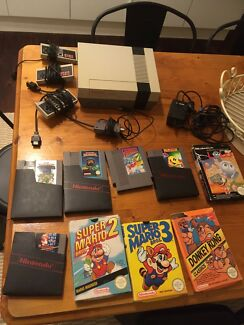 Nintendo Entertainment System (NES) with controllers and 9 games