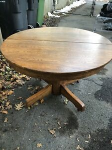 Antique round solid oak pedestal table, has 1 leaf, & on wheels