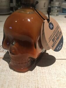 Large bottle of hot sauce in glass skull container