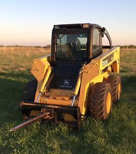 John Deere skid steer with lots of attachments.