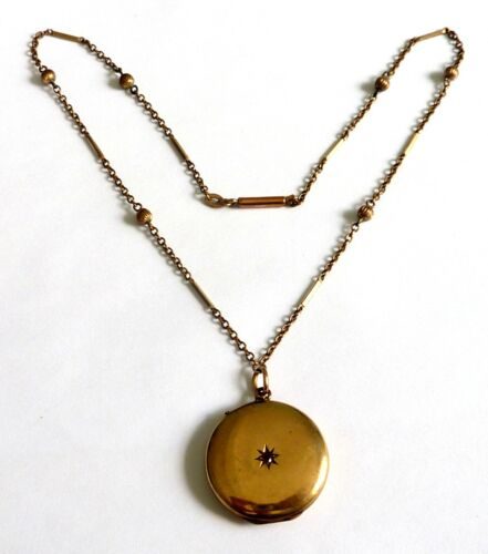 AN EDWARDIAN GOLD CASED LOCKET WITH A CENTRAL RUBY & FANCY ROLLED GOLD CHAIN