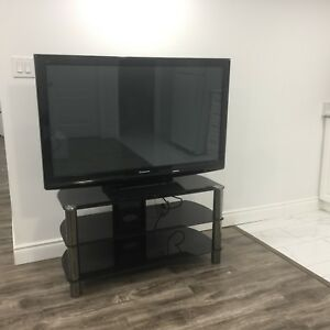 Panasonic Tv with table and remote.