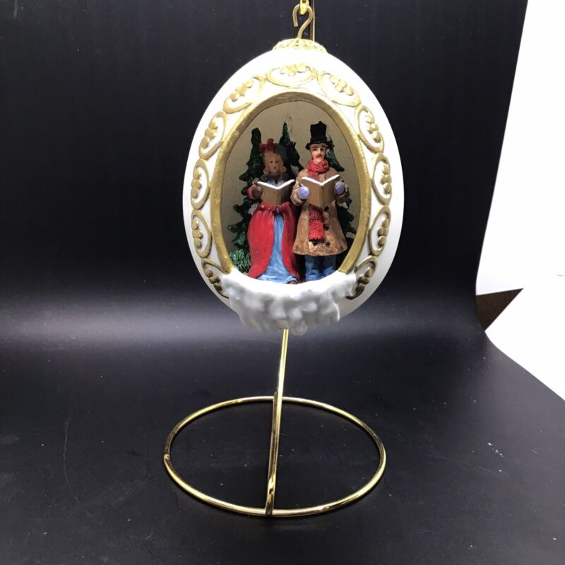 "5-1/4""H PORCELAIN EGG w/ STAND CHRISTMAS SCENE INSIDE MAN & WOMAN CAROLERS"