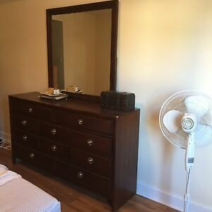 Brown wooden dresser with mirror and modern hand pulls
