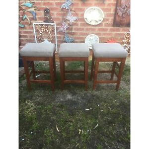 3 timber bar stools with padded seats