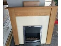Electric fire heater with wooden surround and mantel.
