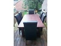 Hardwood dining table and 6 black faux leather chairs