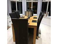 A quality dining table with 4 leather chairs