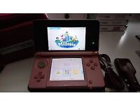 Metallic pink Nintendo 3DS console and accessories