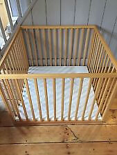 Wooden playpen with white padded base.