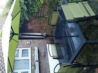 Black garden table with x4 green reclining chairs and green parasol